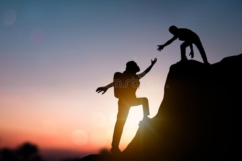 help and improve concept, silhouette people helping other hiker climbing rock and mountain royalty free stock image
