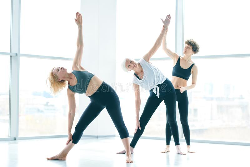 Help of instructor. Two mature active females exercising in gym or fitness center wh8ile young instructor helping one of them royalty free stock image