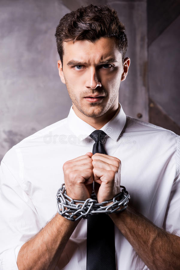 Help me!. Frustrated young man in shirt and tie holding hands clasped while being trapped in stock photos