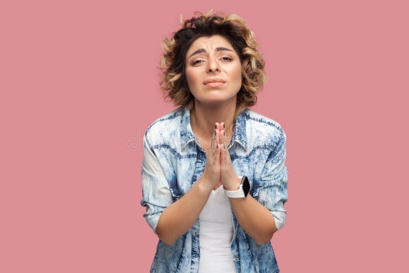 Help me gelieve of te vergeven Portret van zorg droevige jonge vrouw met krullend haar in toevallig overhemd die zich met palm ha stock afbeeldingen