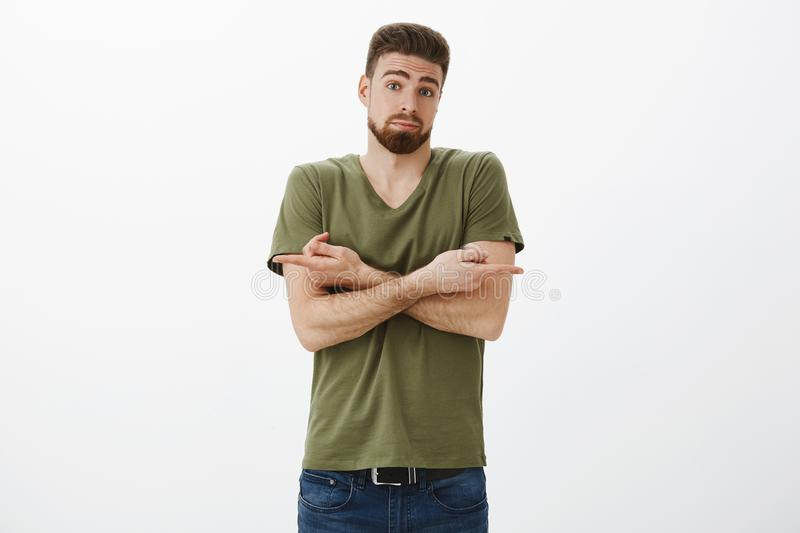 Help me make decision I not know. Portrait of confused and unsure, hesitant cute male customer with beard picking gift. For valentines day cross hands and royalty free stock images