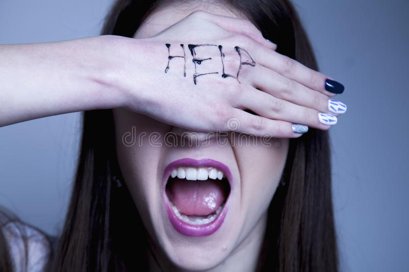 Help me! Woman`s cries for help with painted inscription on her stock image