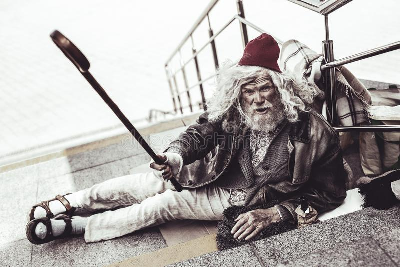 Caucasian beggar giving fallen cane to man passing by. stock image