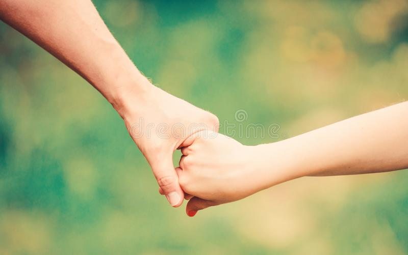Help and support. father hold his child with hand. hands together. family values and love. family bonding time. Hands. Together. concept of supporting stock photos
