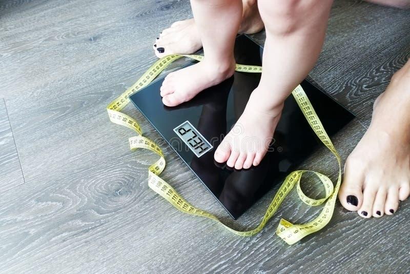 Help uw kind om een gezonde voeding en een levensstijl, met zwaarlijvige jong geitjevoeten op gewichtsschaal, onder de supervisie stock fotografie
