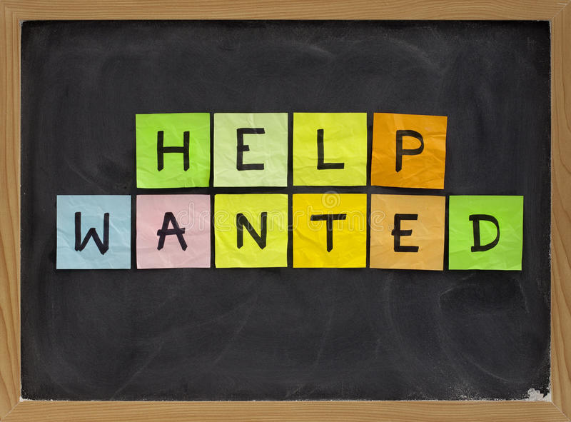 Help wanted. Colorful sticky notes sign on blackboard with white chalk texture royalty free stock images