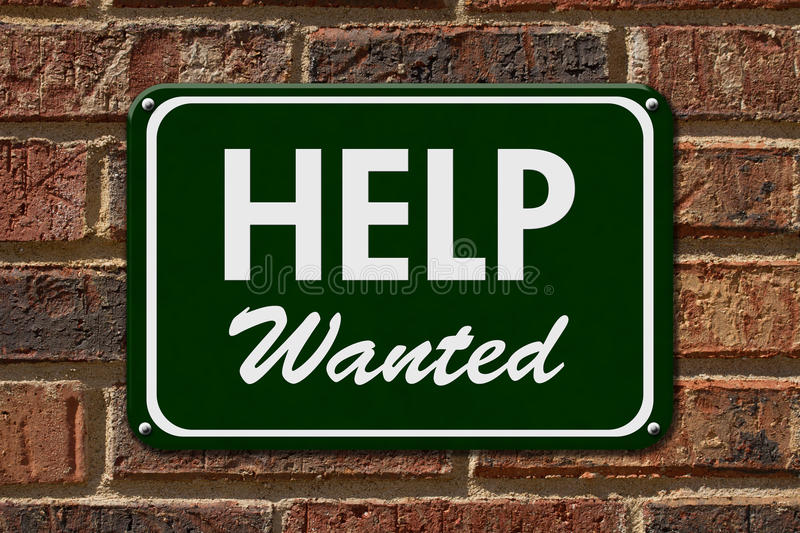 Help Wanted Sign. A green sign with the word Help Wanted with an arrow on a brick wall stock photo