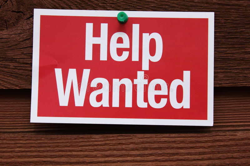 Help Wanted Sign. Red and White Help Wanted Sign on a wood background. Companies are hiring workers as the economy improves. Useful for career and job web sites royalty free stock photos