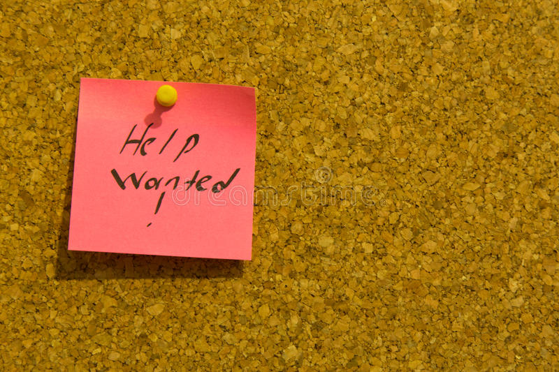 Help wanted sticky note. Pink help wanted stick note on a cork noticeboard stock photos