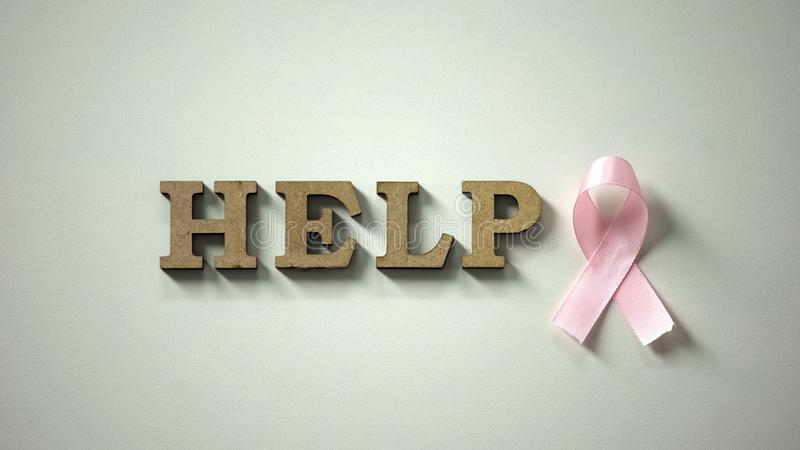 Help word and pink ribbon on table, breast cancer and female health protection stock photography