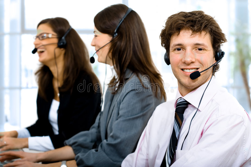 Helpdesk team. Customer service team working in headsets, smiling. Man in front
