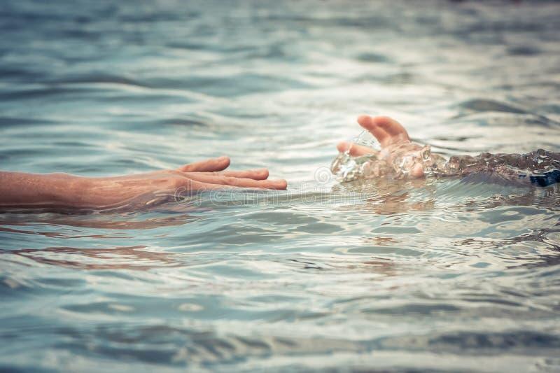 Helpend volwassen hand die kind bereiken verdrinking in de veiligheid van de het waterredding van het waterconcept overhandigen royalty-vrije stock foto's
