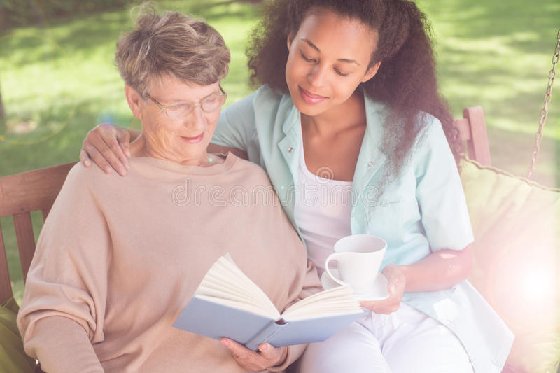 Helpful afroamerican carer. Picture of helpful afroamerican carer and senior woman royalty free stock image