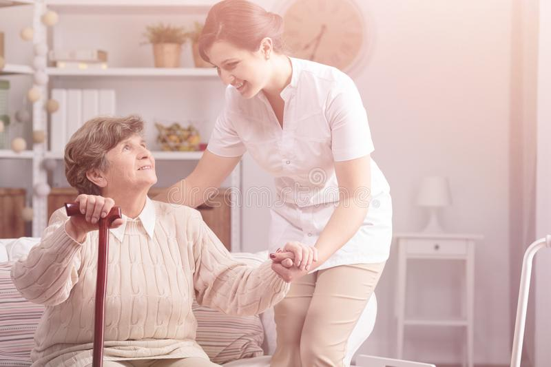 Helpful caregiver supporting smiling senior woman with walking stick stock image