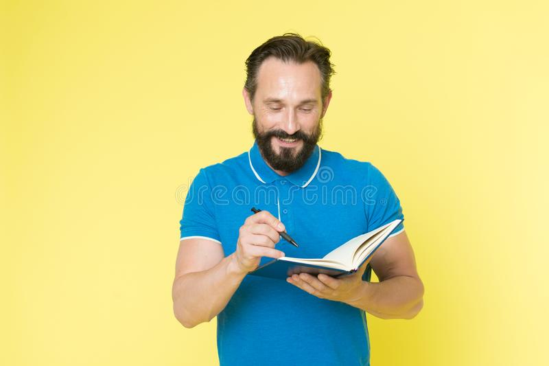Helpful checklist. Man mature bearded guy writing notes to notepad. Check what is done. Daily schedule. Developing stock photo