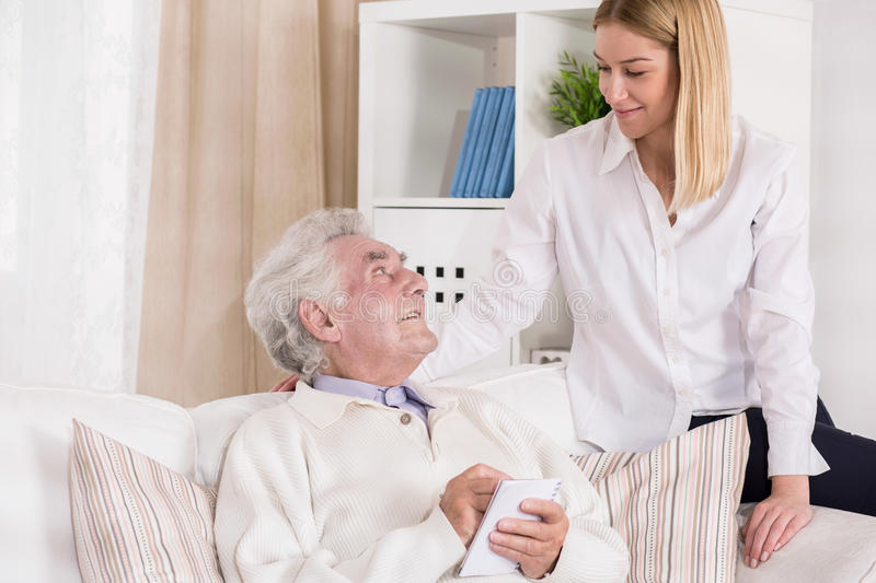 Helpful granddaughter visiting her grandfather. Picture of helpful granddaughter visiting her grandfather in rest home royalty free stock image
