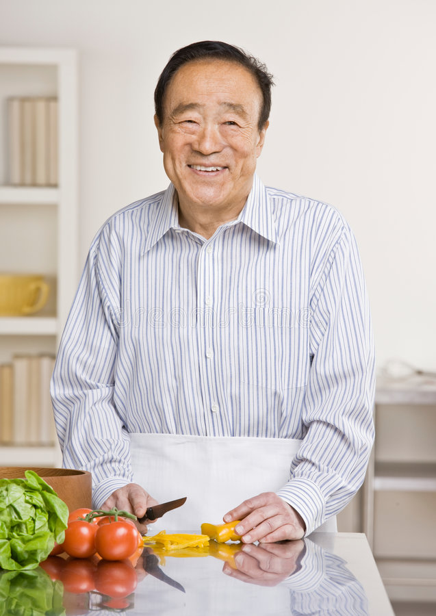 Helpful man preparing salad in kitchen stock photography