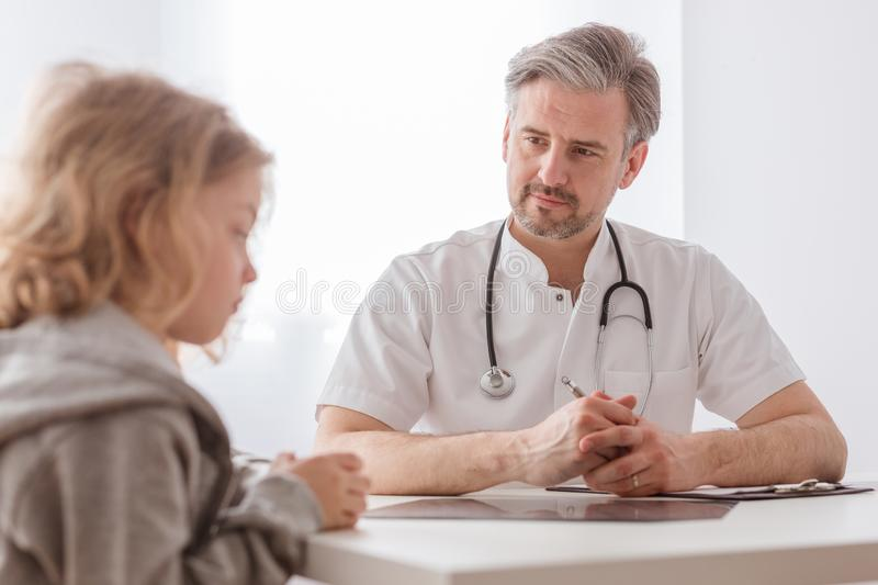 Helpful pediatrician and sick blond boy in a doctor`s office royalty free stock image