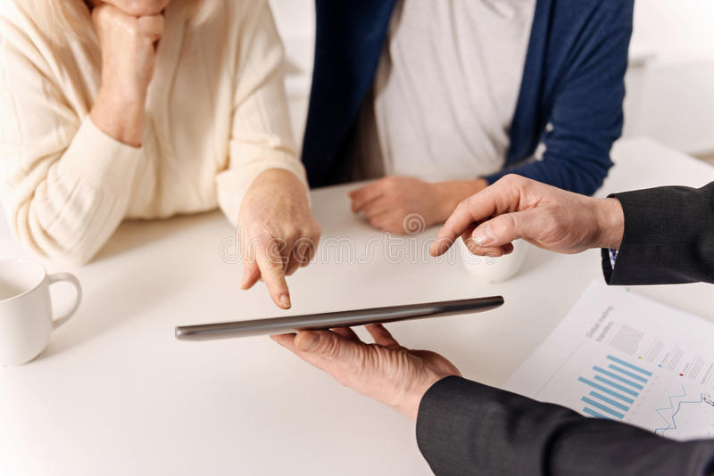 Helpful real estate agent working with aging couple of clients stock images