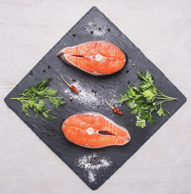 Helpful sports foods, cooking two fresh salmon steak with herbs , spices, top view. Helpful sports foods, cooking two fresh salmon steak with herbs and spices royalty free stock photography