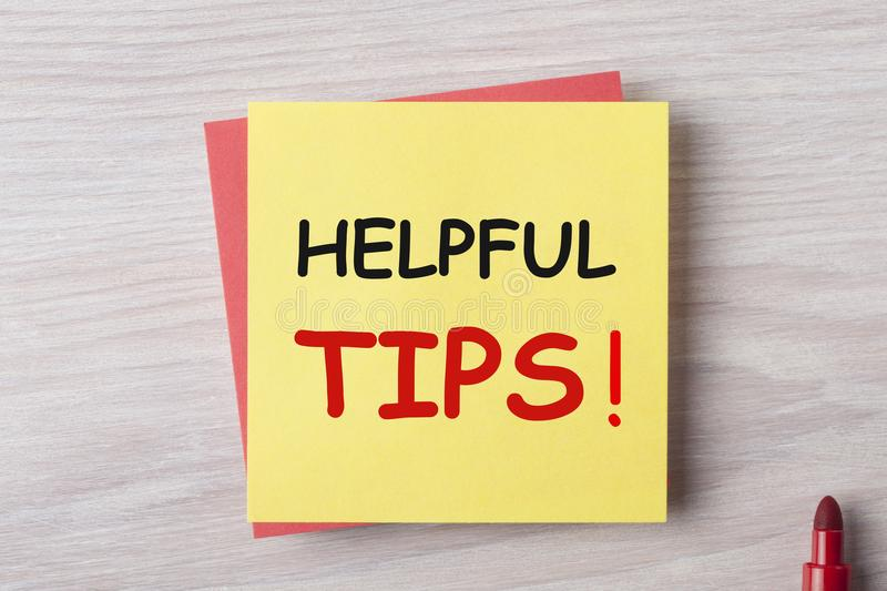 Helpful Tips Concept. HELPFUL TIPS written on yellow note and marker pen on wooden desk. Business Concept royalty free stock photo