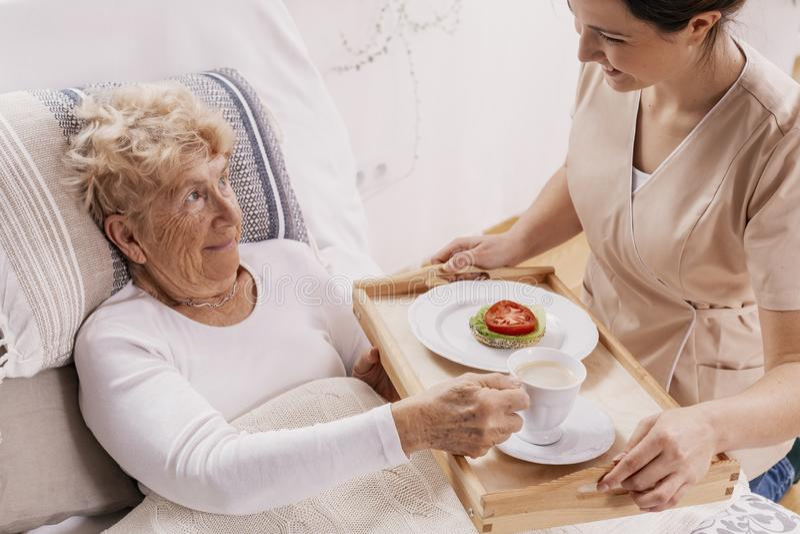Helpful volunteer in beige uniform serving coffee to senior female patient.  stock photos