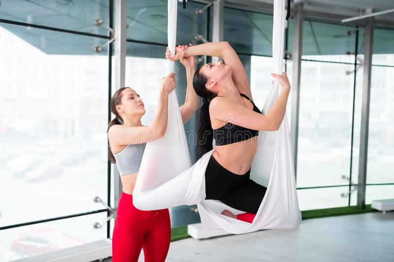 Helpful yoga trainer assisting her client doing aerial yoga stock photo