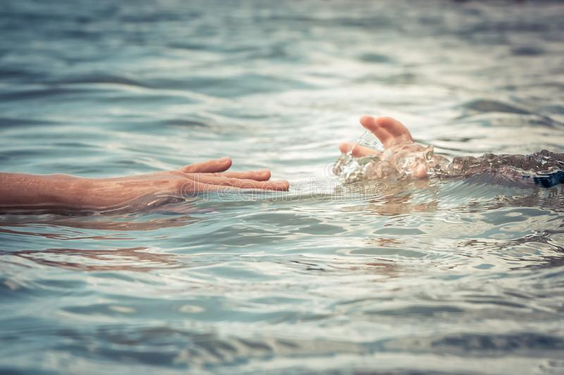 Helping adult hand reaching child hand drowning in water concept water rescue safety royalty free stock photos