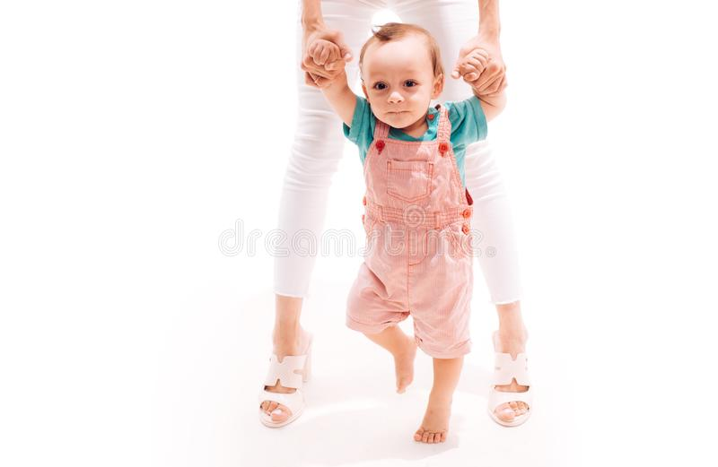 Helping baby learn to walk. Small child walking with help, motor skills. Little boy child develop gross motor activity. Toddler stage of development. Adorable stock image