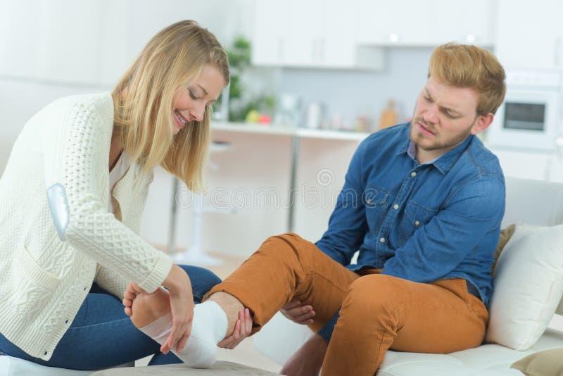 Helping boyfriend with damaged ankle. Girlfriend stock photos