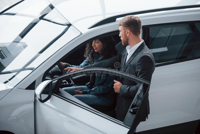 Helping girl to decide. Female customer and modern stylish bearded businessman in the automobile saloon stock photography