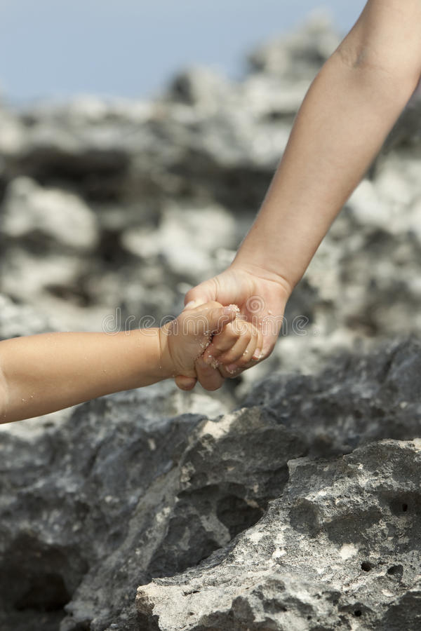 A helping hand. My six years old son's hand helping his little brother climb up stock images