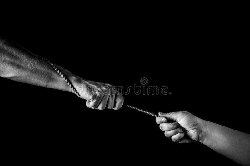 Helping hand concept, hands pulling rope, giving help, care and support, reaching out, saving. royalty free stock photography