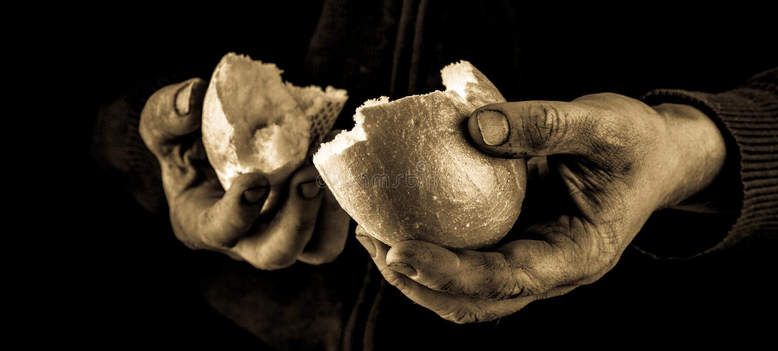 Helping hand giving a piece of bread. Poor Man dividing and sharing Bread, Helping Hand Concept. stock images