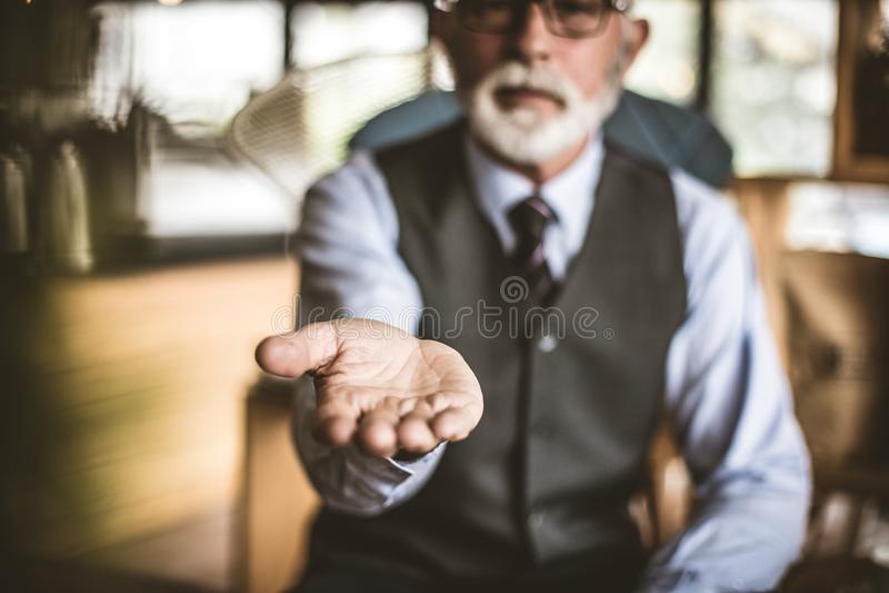 Helping hand. Senior businessman. Focus on hand. stock images