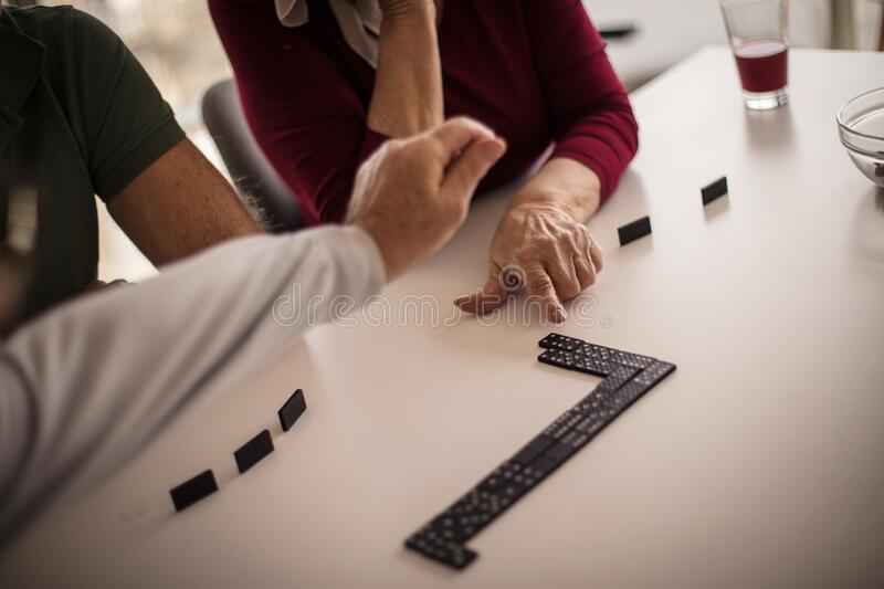 Helping hand. Senior people playing dominoes  at home. Focus is on hands royalty free stock images