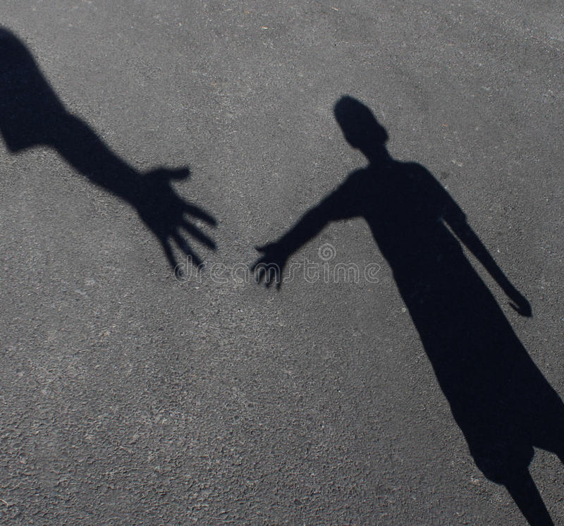 Helping Hand. With a shadow on pavement of an adult hand offering help or therapy to a child in need as an education concept of charity towards needy kids and royalty free illustration