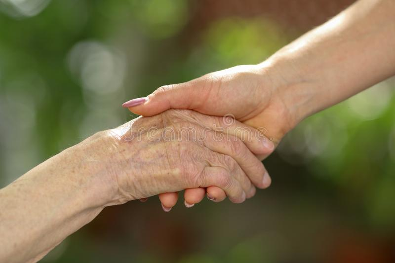 Young caregiver holding seniors hands. Helping hands, care for the elderly concept. Young caregiver holding seniors hand. Elderly concept. Hands of young woman stock image