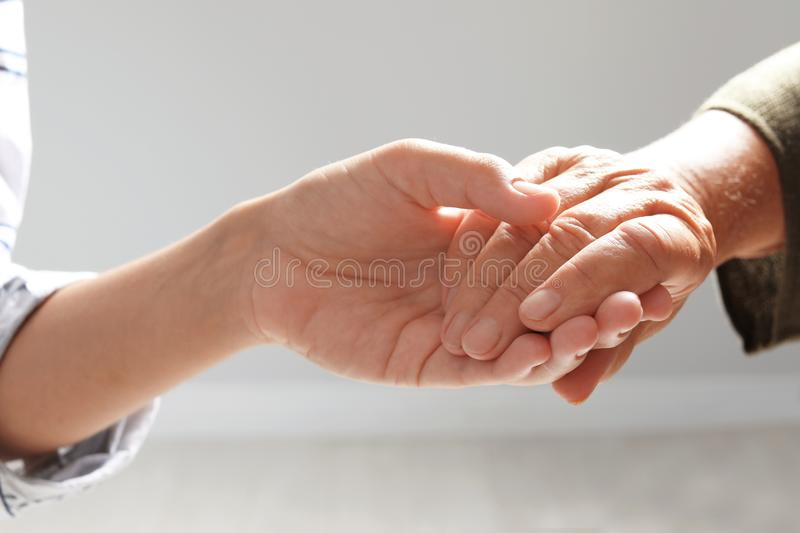Helping hands on grey background, closeup. Elderly care concept royalty free stock photography