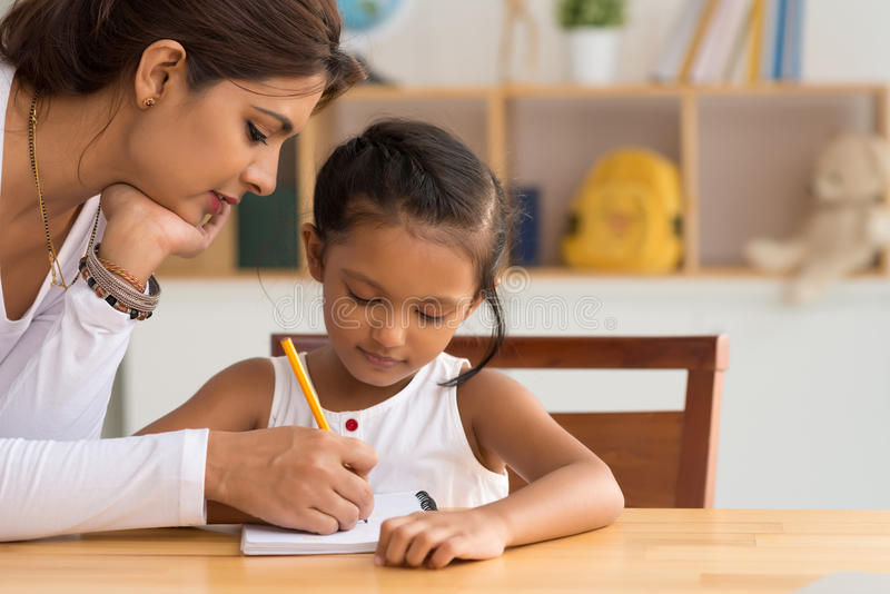 Helping with homework. Beautiful Indian women helping her daughter with homework