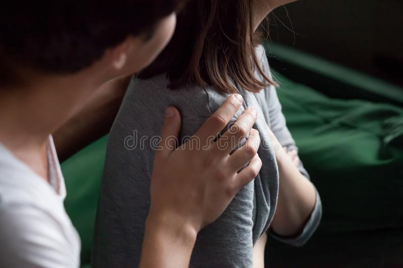 Helping male hand holding female shoulder closeup, psychological. Helping male hand holding female shoulder close up view, caring understanding men husband royalty free stock image