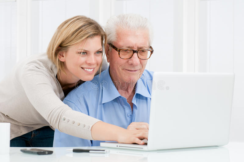 Helping with new computer. Happy smiling young girl teaching and showing new computer technology to her grandfather stock photography