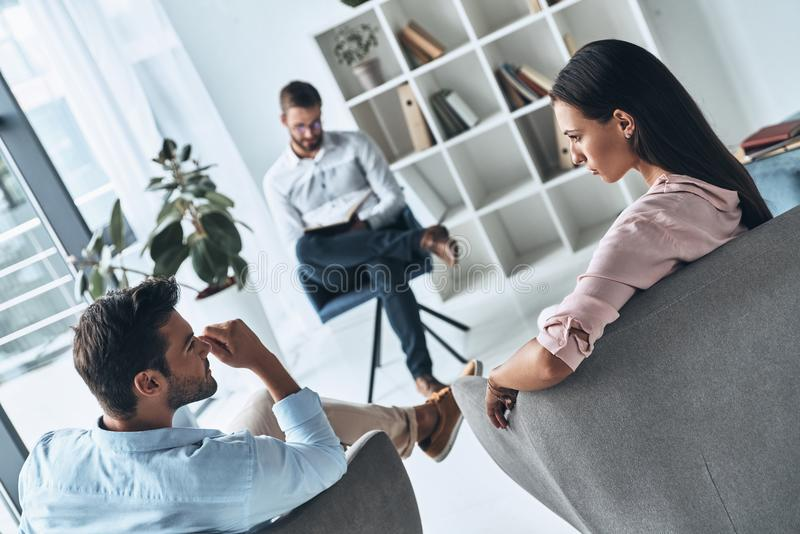 Helping others. Young married couple talking while sitting on the therapy session with psychologist stock images
