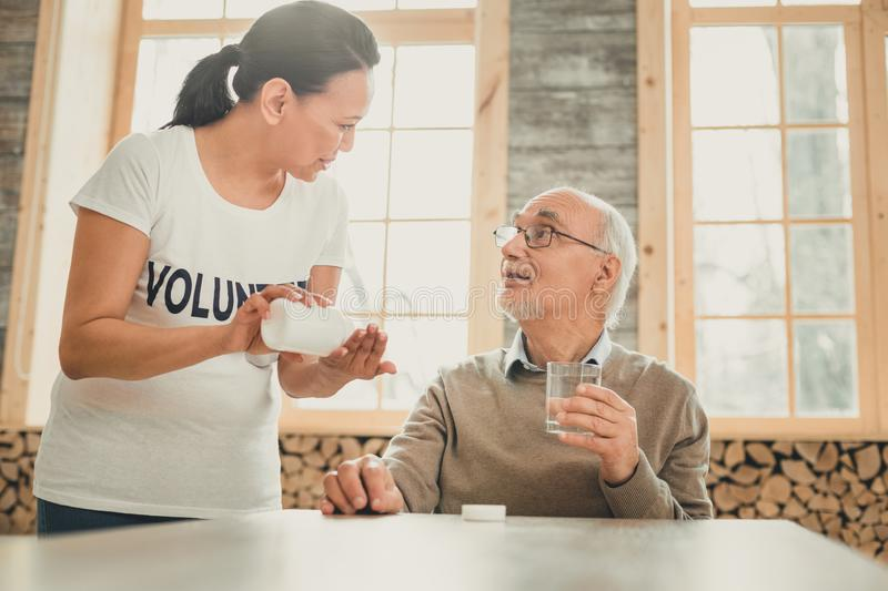 Thoughtful adult woman helping grey-haired man with medication. Helping pensioner. Thoughtful adult women helping grey-haired men with medication while he royalty free stock photo