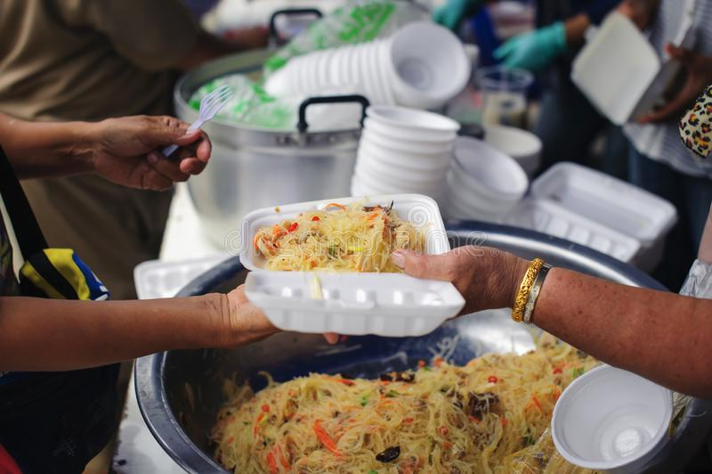 Helping people by donating food: The concept of feeding stock image