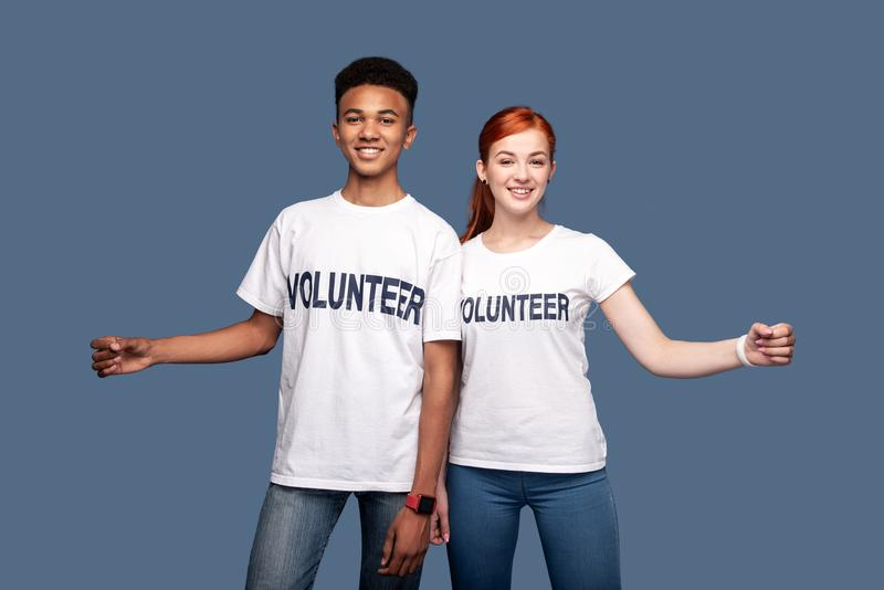 Positive young volunteers looking at you. Helping people. Positive young volunteers looking at you while standing against blue background royalty free stock photos