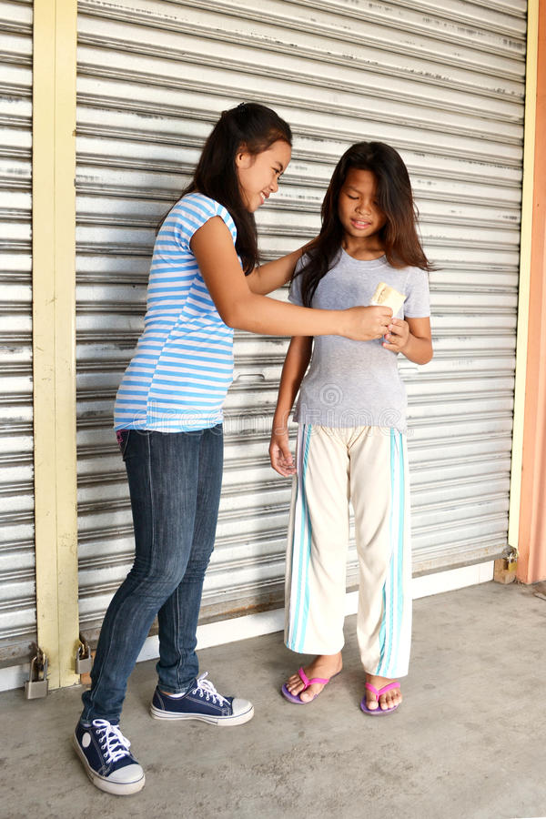 Helping Poor People. Young Asian lady helps poor little girl in the street by giving her a sandwich stock image