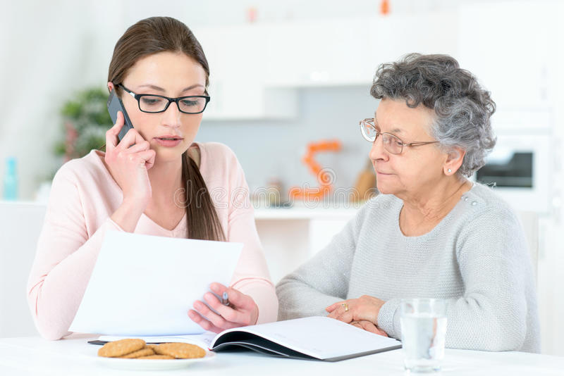 Helping senior lady with finances royalty free stock photography