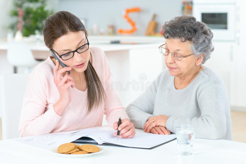 Helping senior lady with finances royalty free stock image