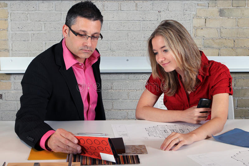Helping to choose fabrics. Salesmen helping a client to choose fabrics for furniture stock photography